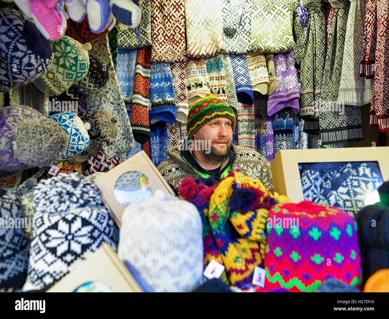 Riga, Latvia - December 25, 2015: Festively dressed man selling woolen clothes at Riga Christmas Market. Warm mittens, - Stock Image