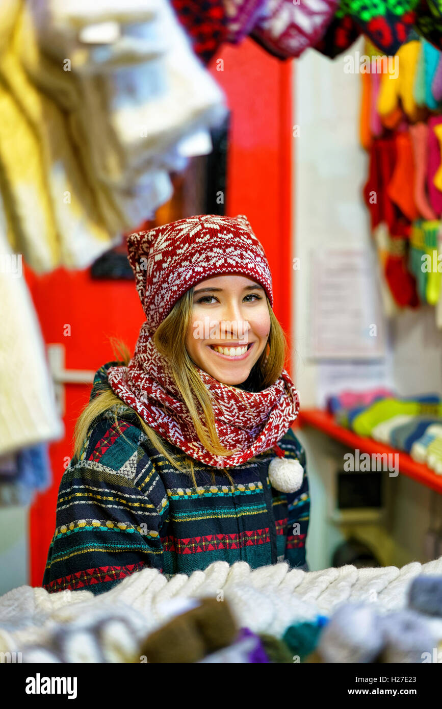 Riga, Latvia - December 24, 2015: Young and festively dressed woman pictured while trading with various warm clothes - Stock Image