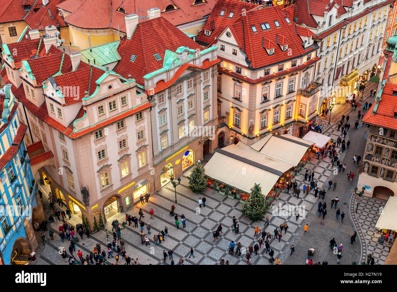 View from above on people walking among shops, restaurants and houses during Christmas time in Prague. - Stock Image