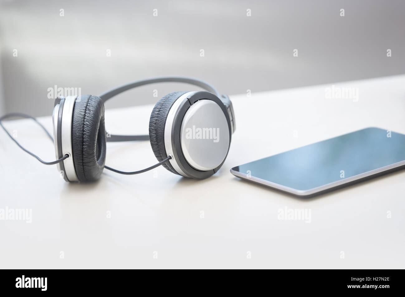 Headphones and digital tablet on a table - Stock Image