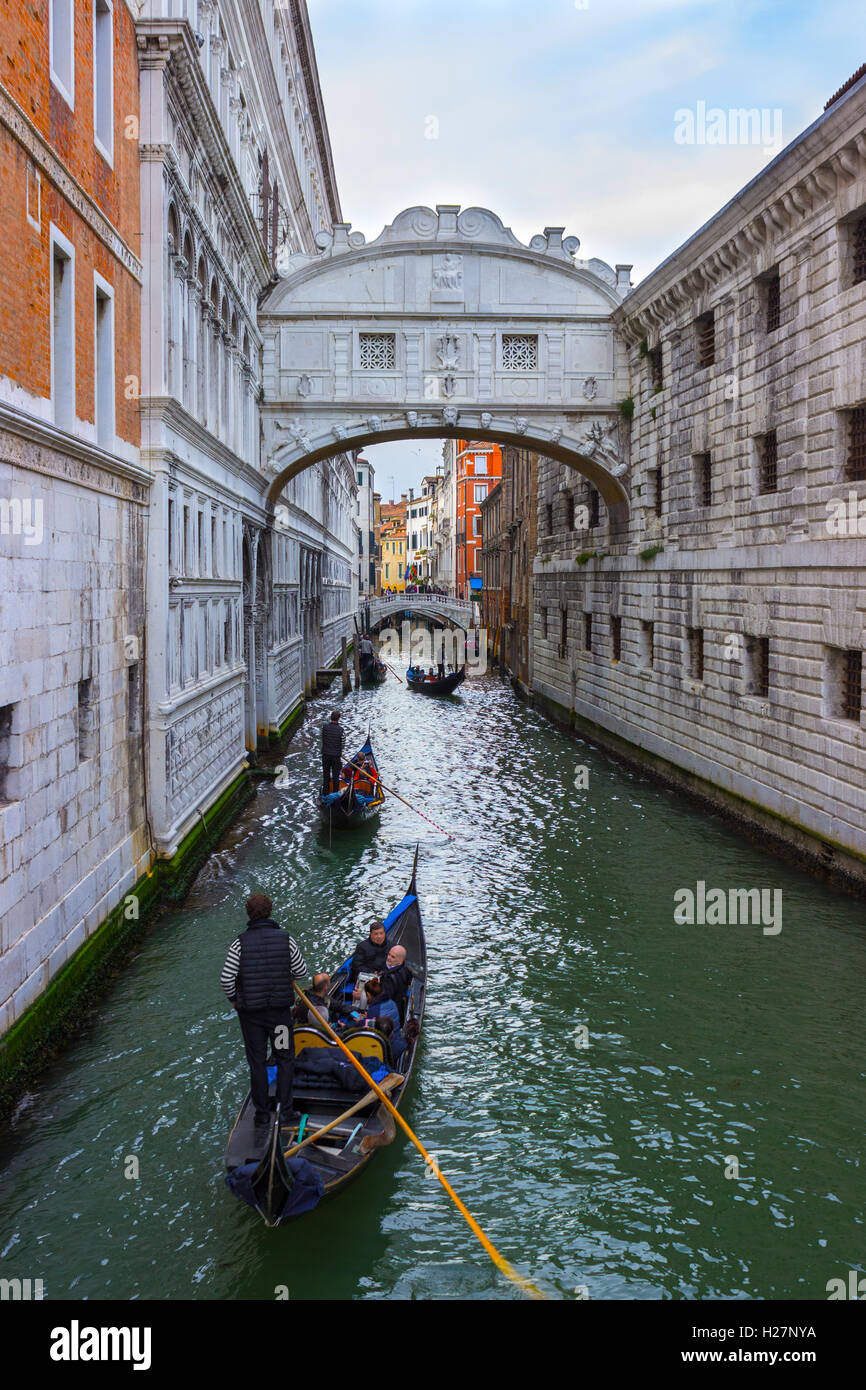 ITALY, VENICE - APRIL 2, 2016: Gondolier on gondola on the Bridge of Sight taking tourist for a ride. View of the Stock Photo