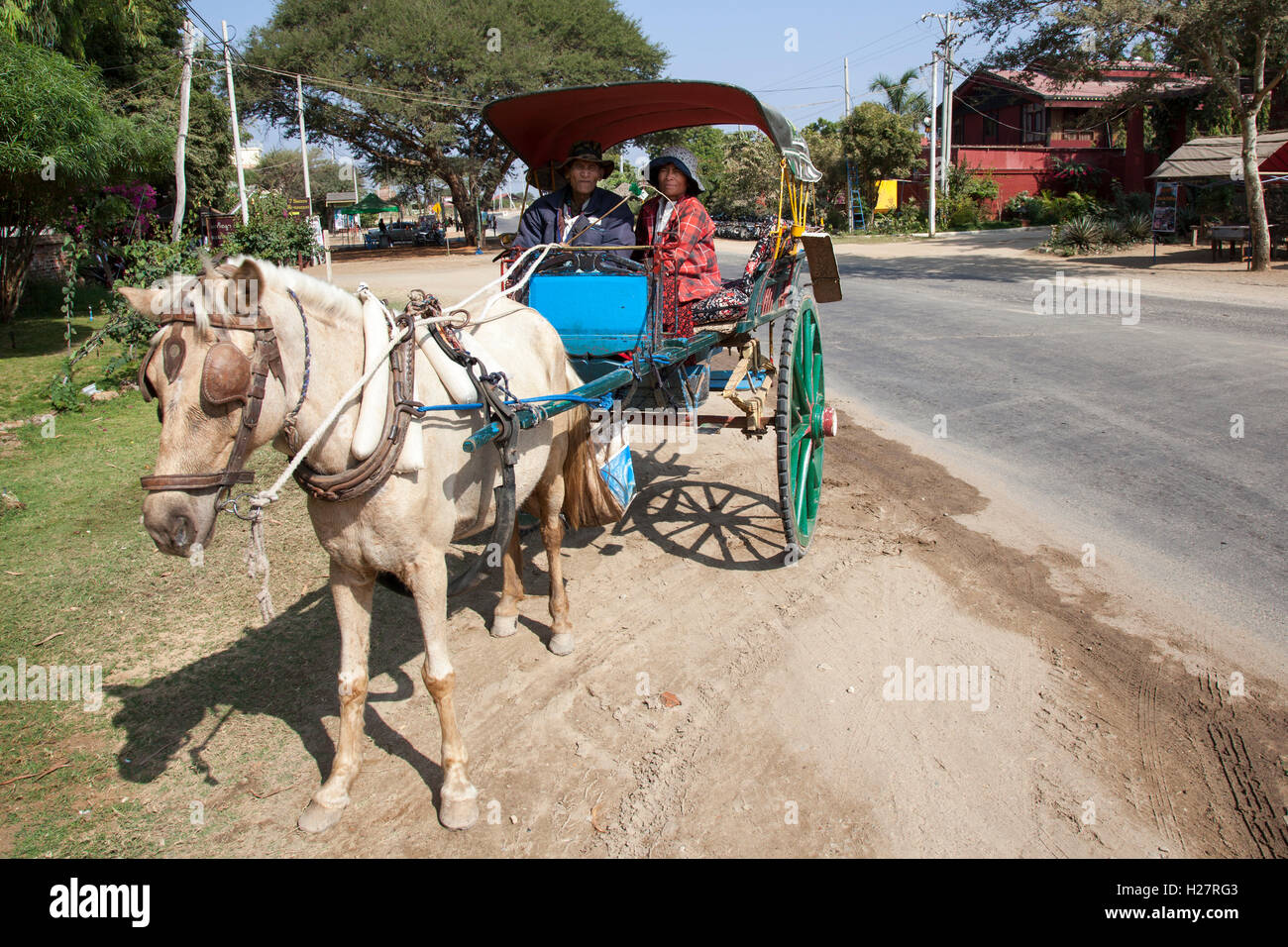 An old and faded calash with a couple of coach drivers waiting for passengers, at New Bagan (Myanmar). Vieille calèche - Stock Image