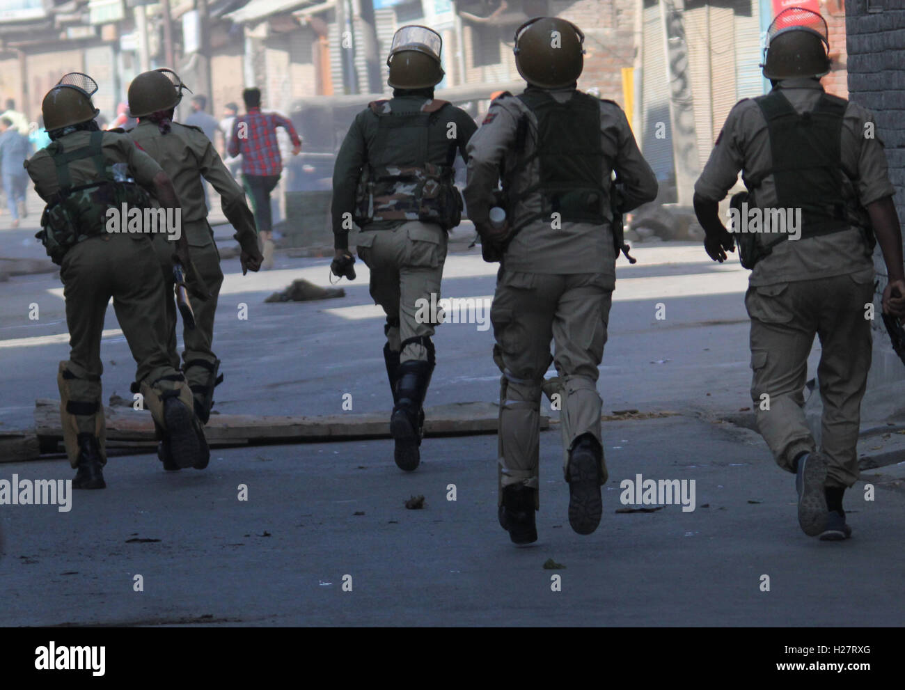 Srinagar, India. 25th Sep, 2016. Kashmiri Muslim protestors run for cover as they are chased by armed forces in - Stock Image