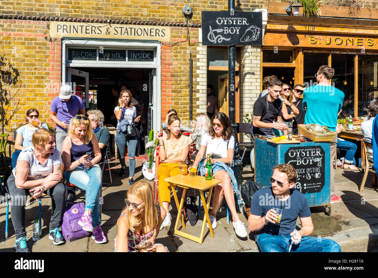 London, United Kingdom - September 11, 2016: Columbia Road Flower Sunday market. People relaxing in cafes - Stock Image