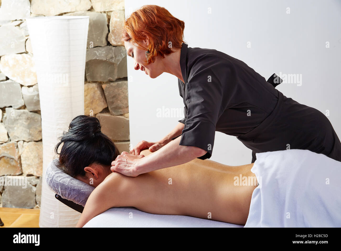 massage in woman back with physiotherapist indoor - Stock Image