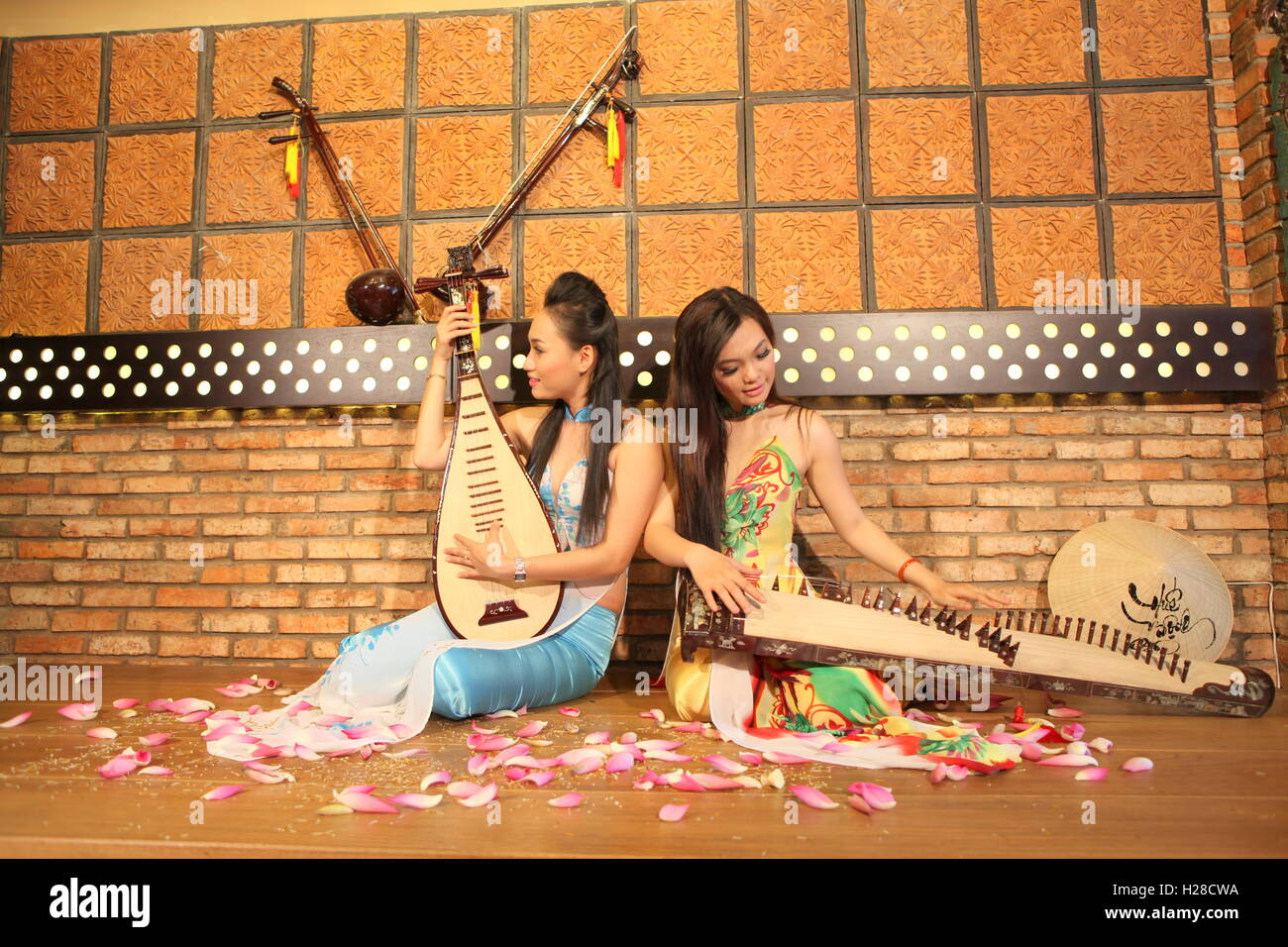 Vinh Long, Vietnam - November 4, 2015: Two young girls are playing Vietnamese traditional instruments in a restaurant Stock Photo