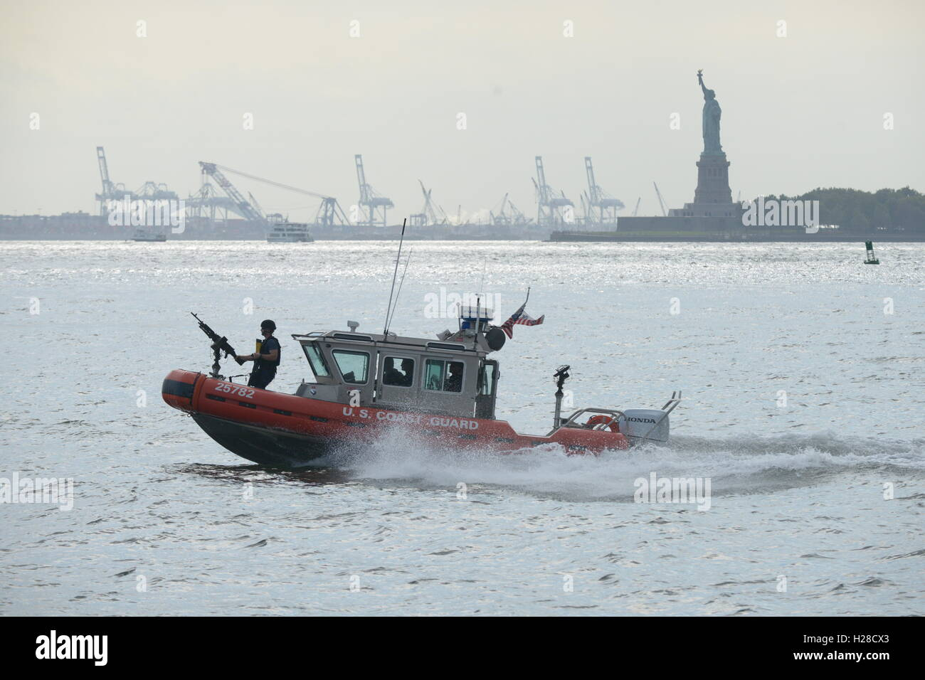 U.S. Coast Guardsmen patrol the New York Harbor near the Statue of Liberty during the anniversary of the 911 terrorist - Stock Image