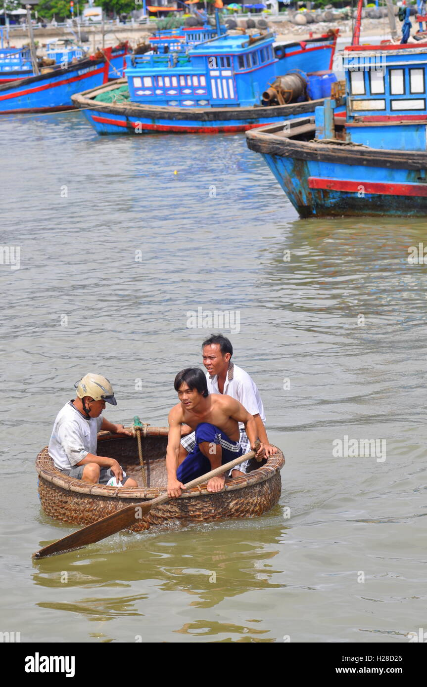Nha Trang, Vietnam - October 5, 2011: Fishermen are swimming from their vessels to the seaport in a basket boat - Stock Image