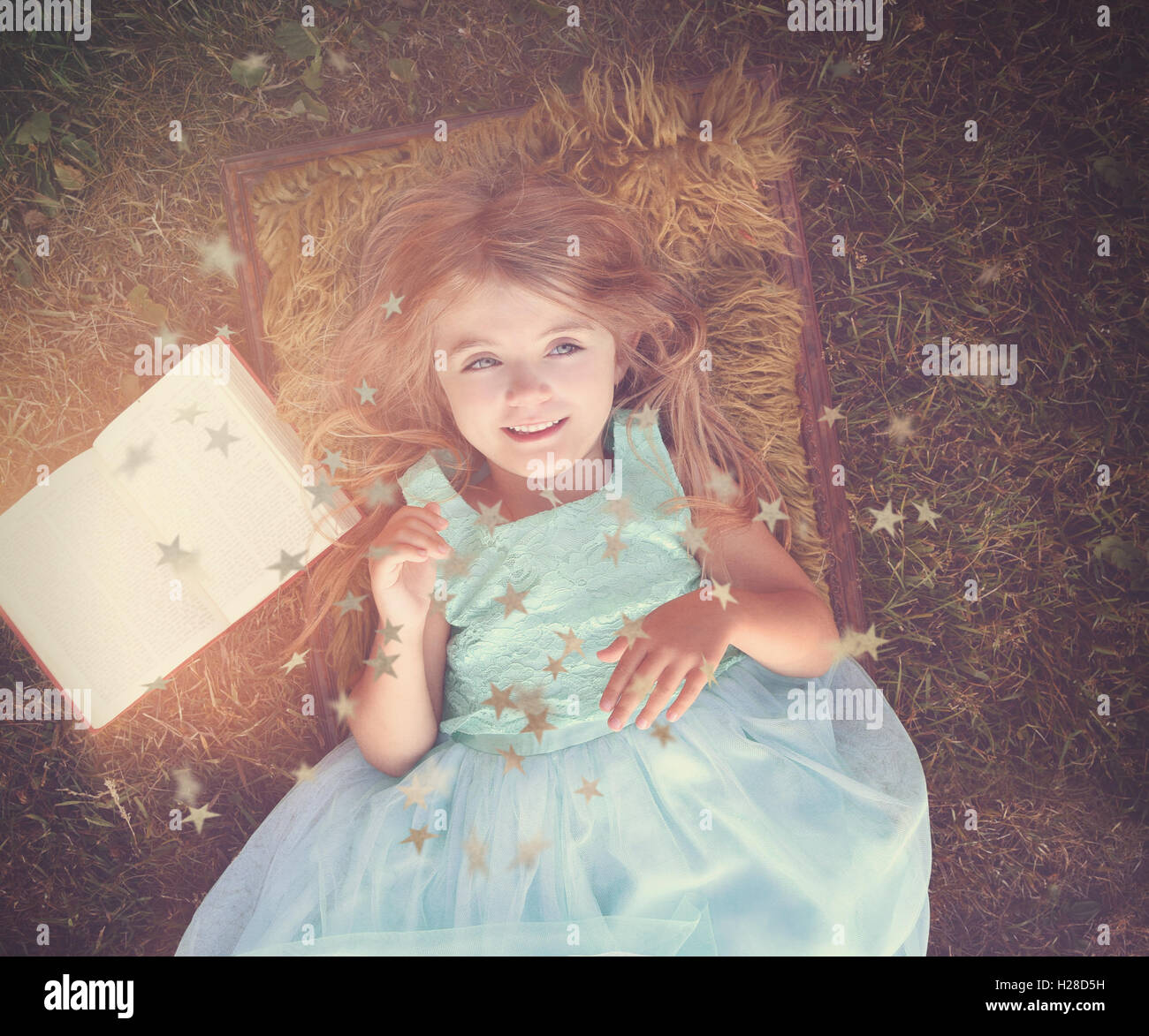 A happy pretty girl is laying on the grass outside with a story book for a mystery, imagination or fairy tale concept. - Stock Image