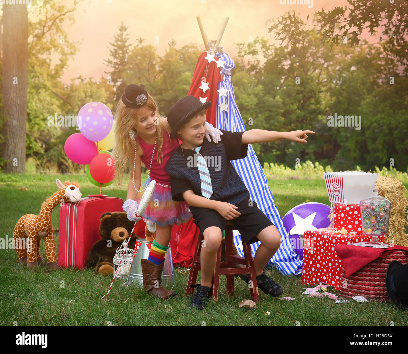 Two children are playing outside dressing up as carnival people at a circus party for an imagination or creativity - Stock Image