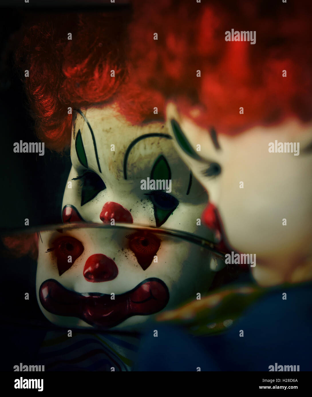 A closeup of a scary evil clown toy doll looking in a broken mirror that could be possessed with evil for a halloween. - Stock Image