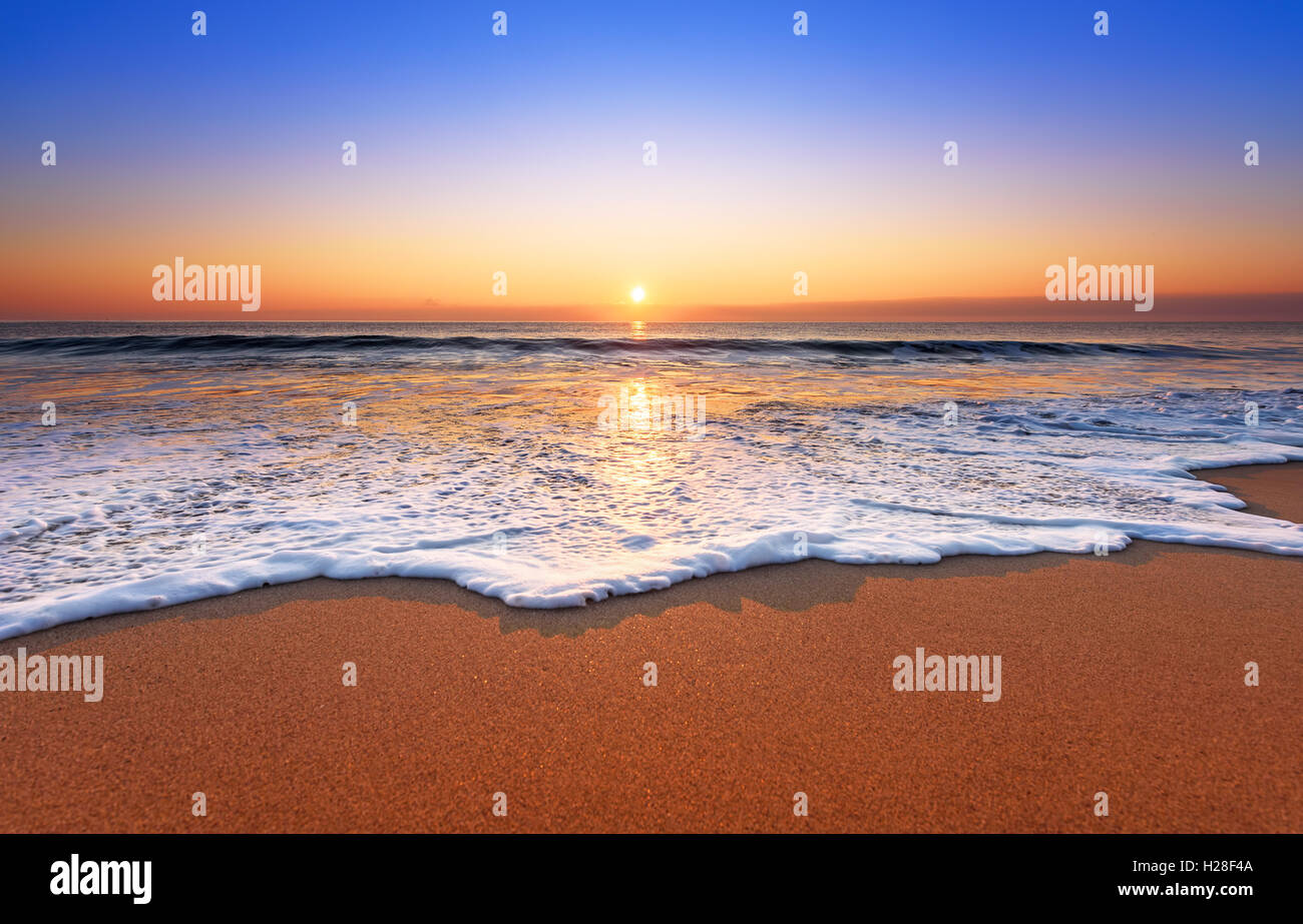 Majestic ocean sunset with a breaking wave. - Stock Image