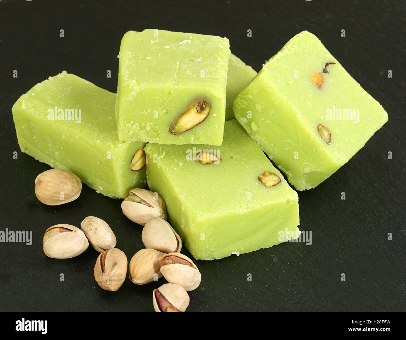 five pieces of pistachio barfi with nuts on a dark slate - Stock Image