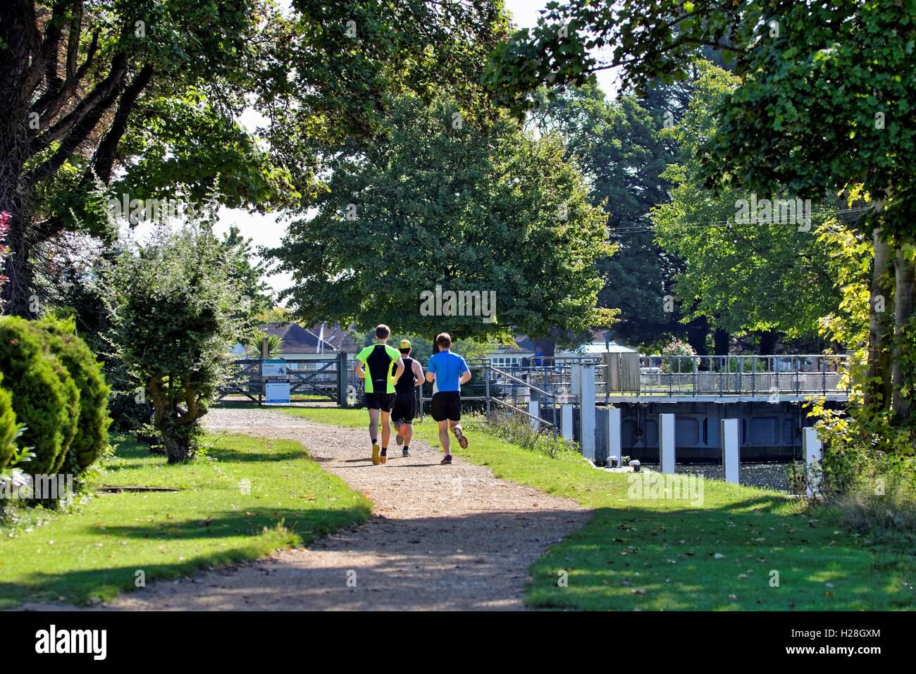 Three young men running on towpath at Penton Hook,Laleham Surrey UK - Stock Image