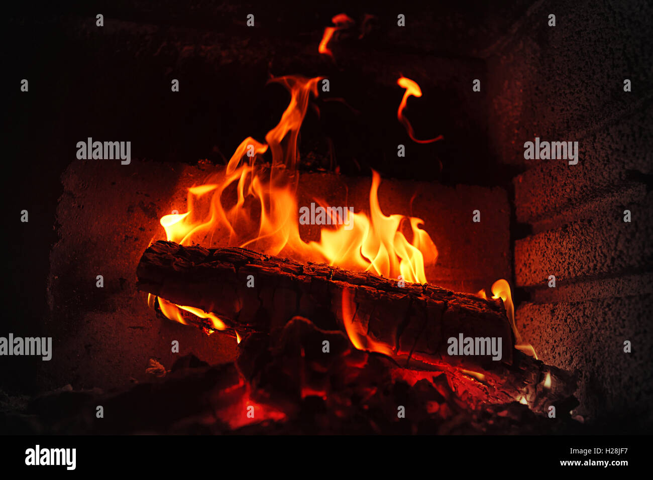 Burning wood in brick fireplace - Stock Image