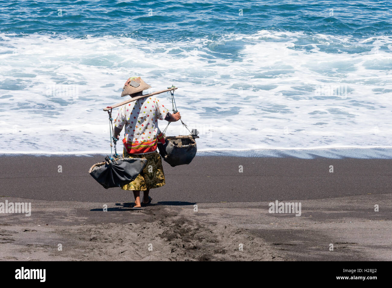 Woman carrying a teku-teku to collect sea water that later will be splashed on the sand to extract the salt. - Stock Image