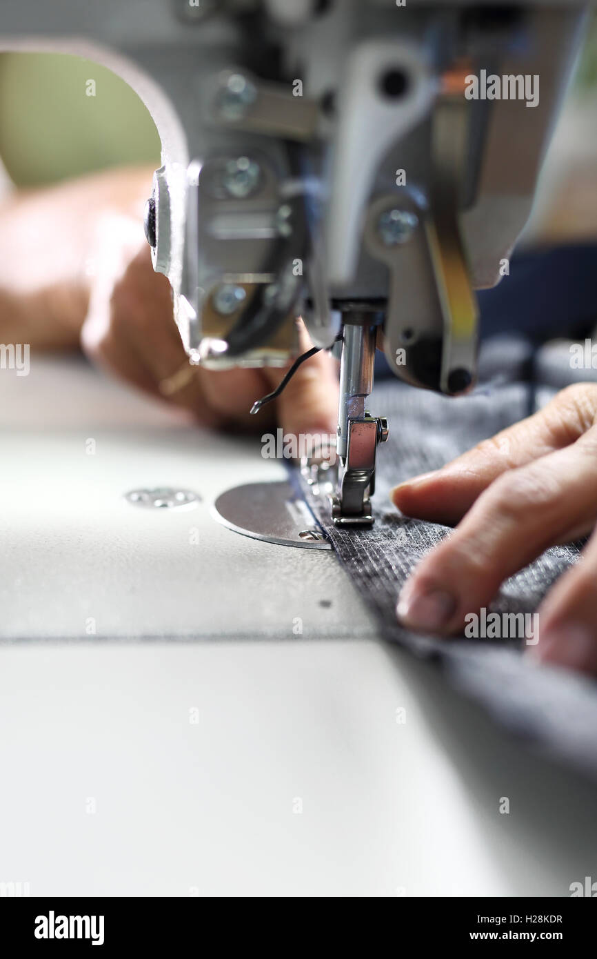 The production plant, sewing clothes by seamstresses on the sewing machine - Stock Image