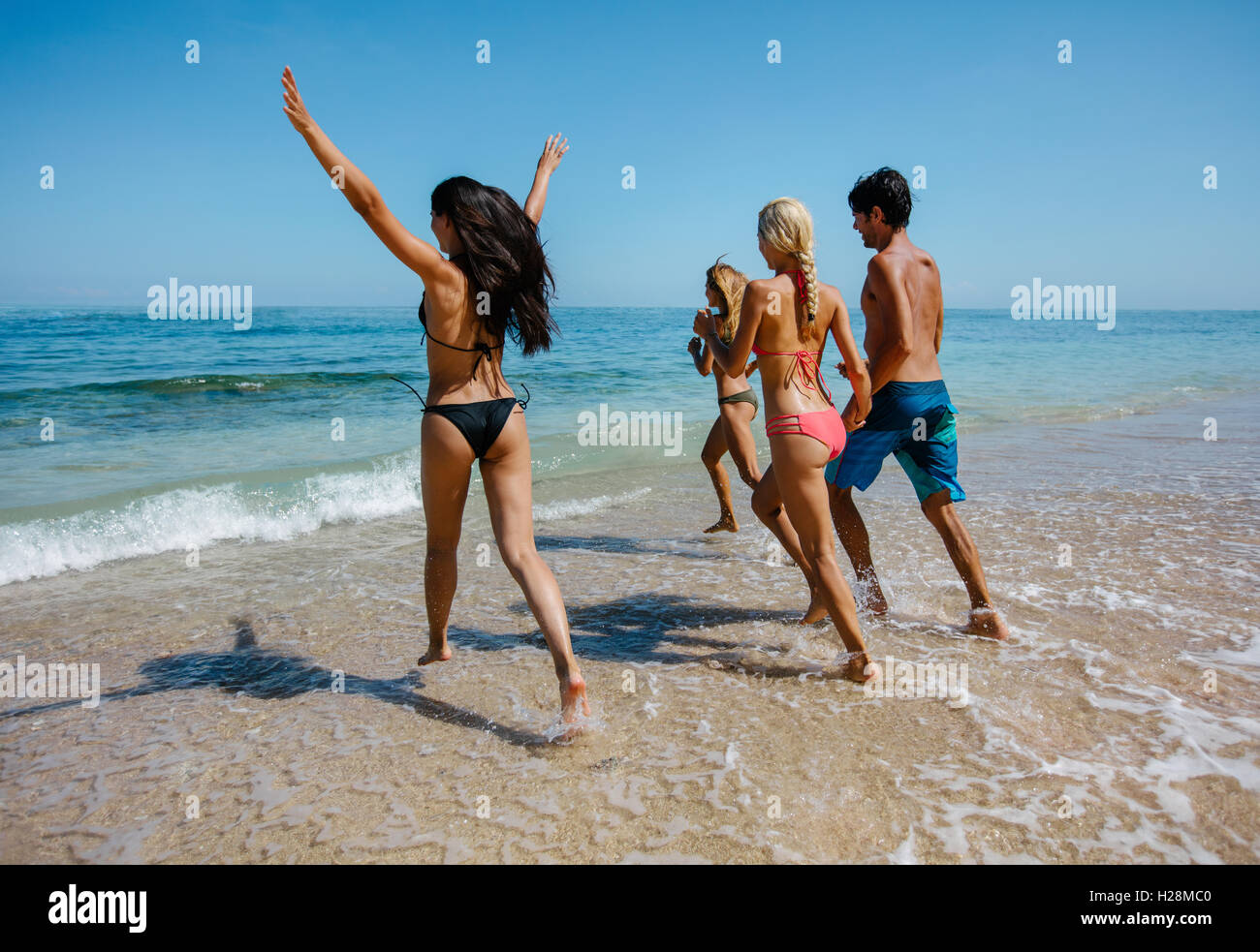Group of happy friends running into sea water. Active people having fun on the beach on vacation. Tourists going - Stock Image