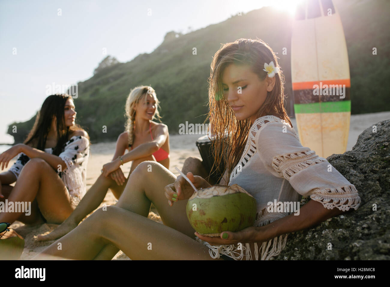 Portrait of beautiful young woman with fresh coconut and friends sitting in background on the beach. Group of young - Stock Image