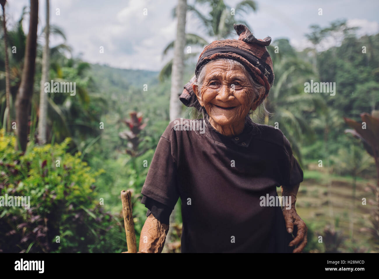 Portrait of happy senior woman with a cane in village. Smiling old female outdoors in countryside. - Stock Image
