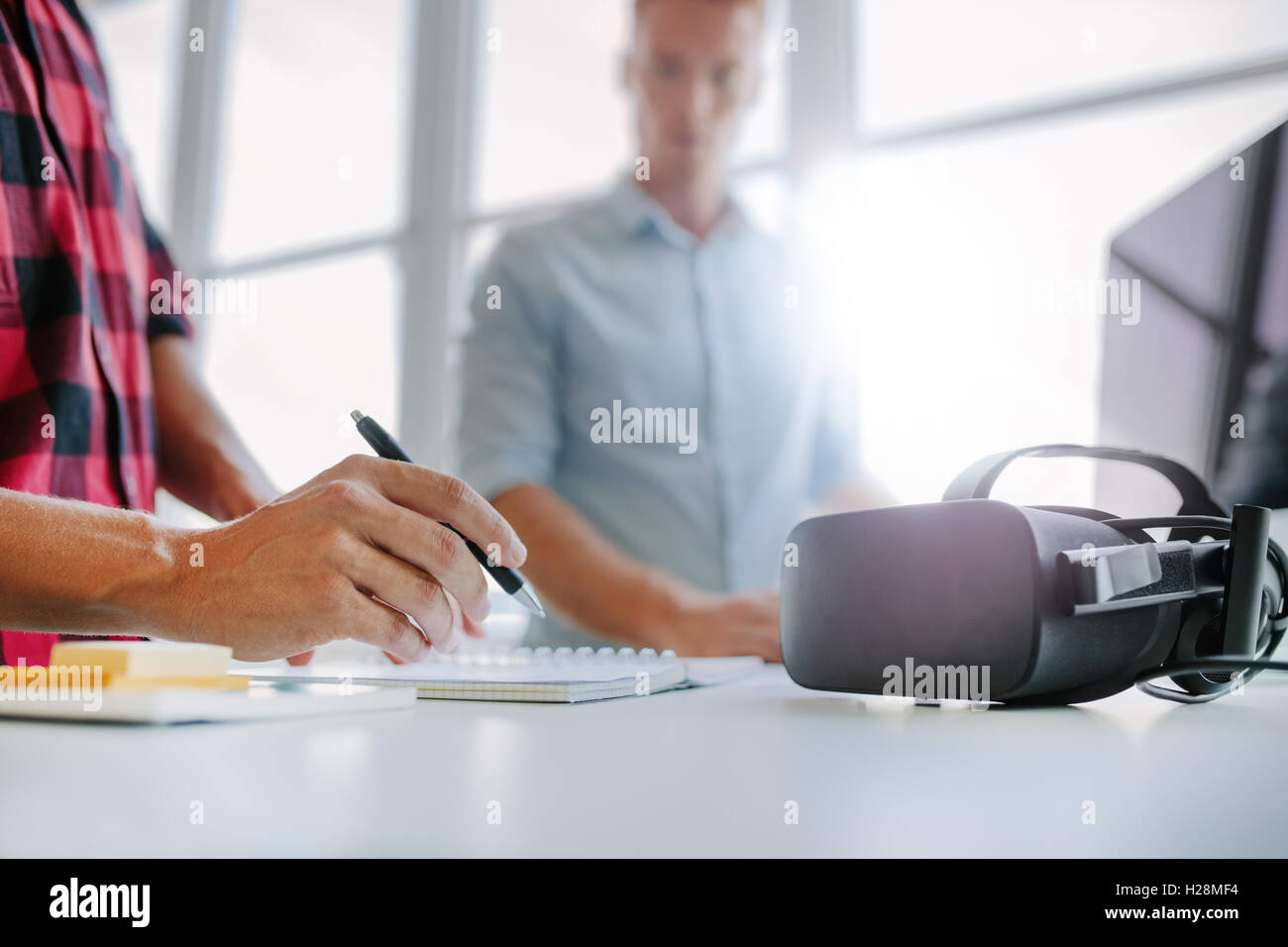 Virtual reality glasses on table with two men working in office.  Man writing colleague using computer in background. - Stock Image