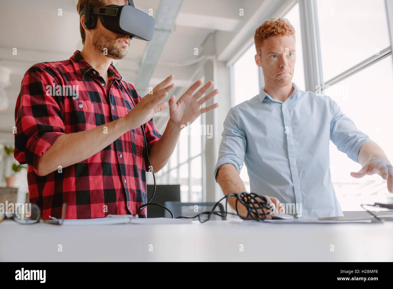 Developers testing an augmented reality device with a broad range of uses from gaming to visual aid. Young man wearing - Stock Image