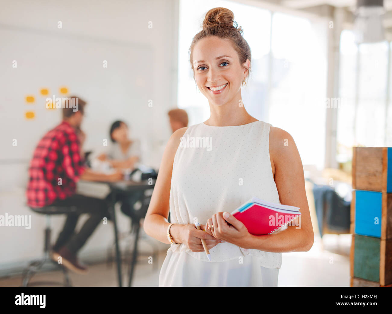 Portrait of beautiful young woman holding notepad with colleagues meeting in background. Business woman in casuals - Stock Image