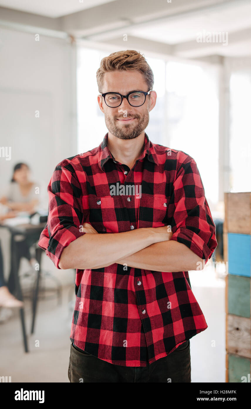Portrait of happy young startup owner standing in office with coworkers meeting in background. - Stock Image