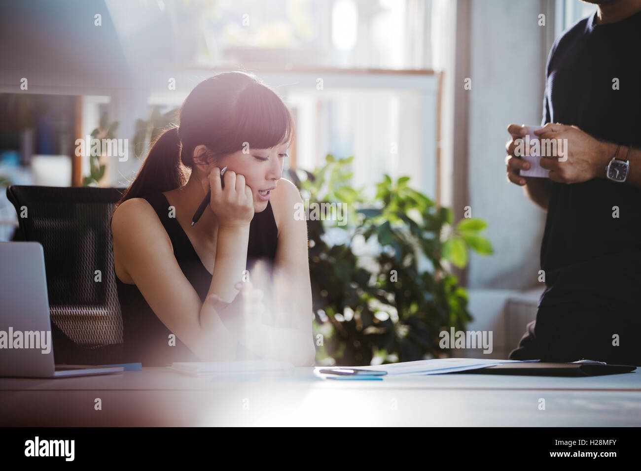 Shot of young woman sitting at her desk and talking with male colleague standing by. Coworkers working together Stock Photo