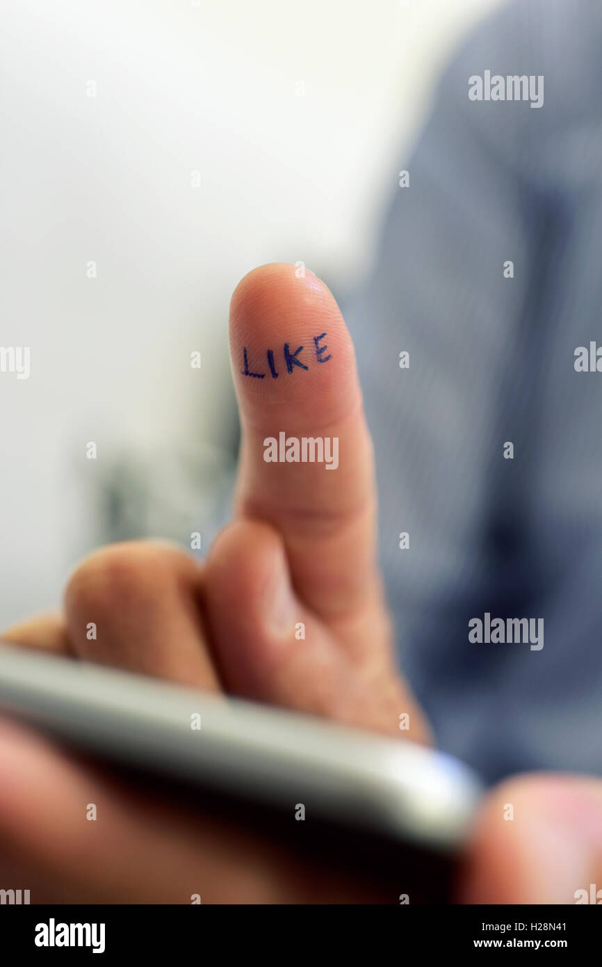 closeup of the hand of a young caucasian man using a smartphone with the word like written in his forefinger - Stock Image