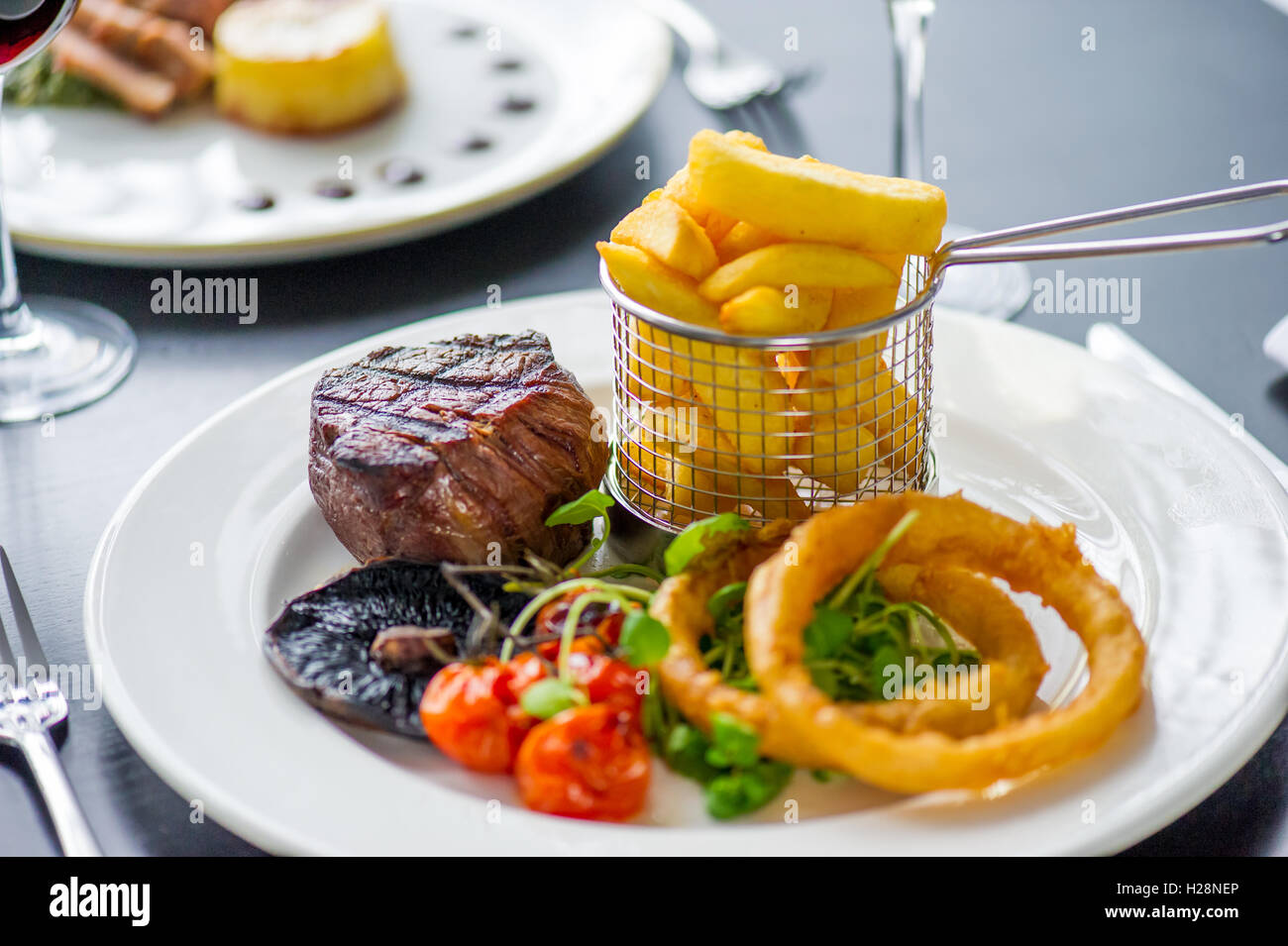 A fillet steak with onion rings and chips - Stock Image