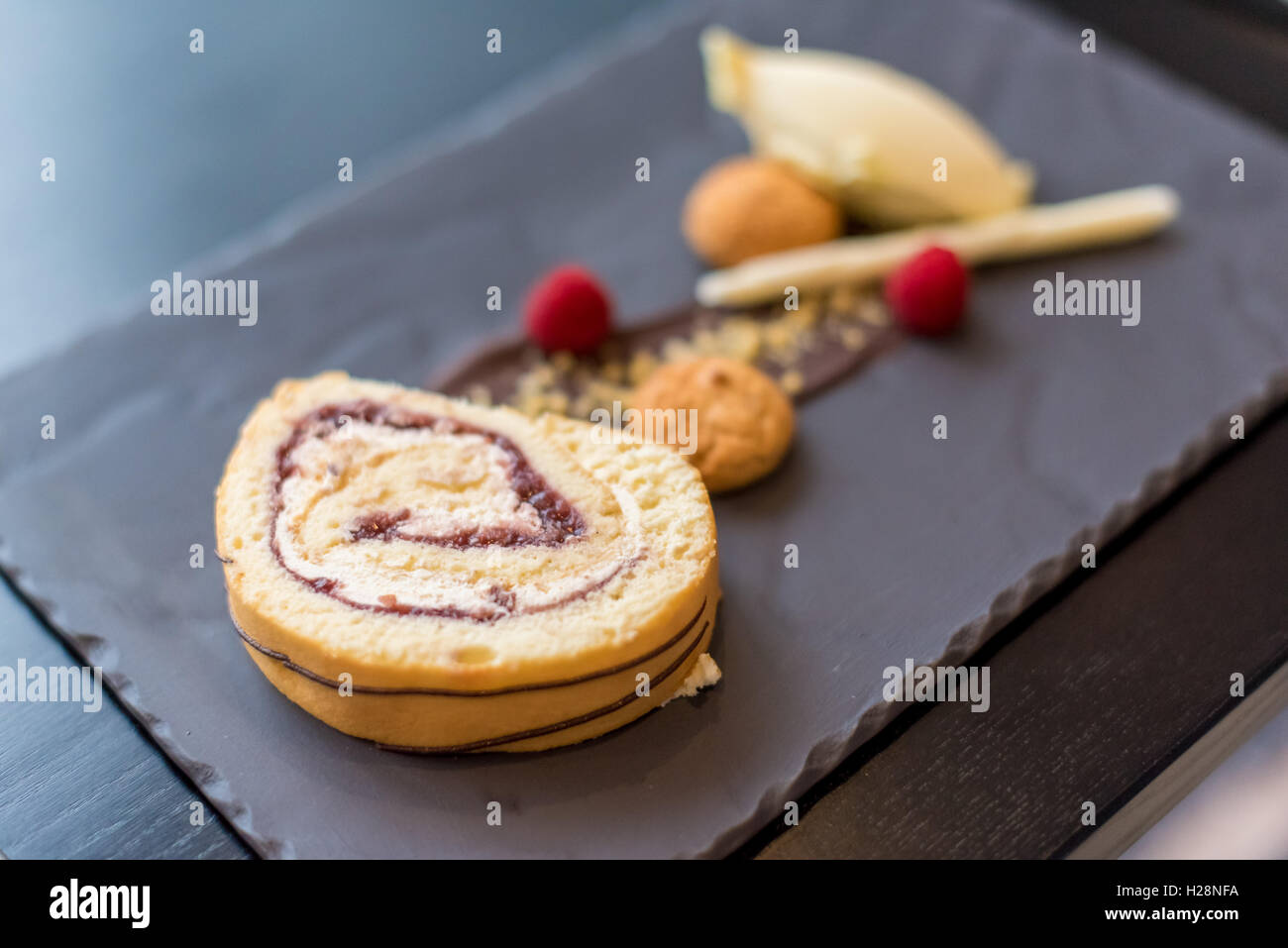 A Swiss roll sponge dessert with ice cream on a slate backdrop - Stock Image
