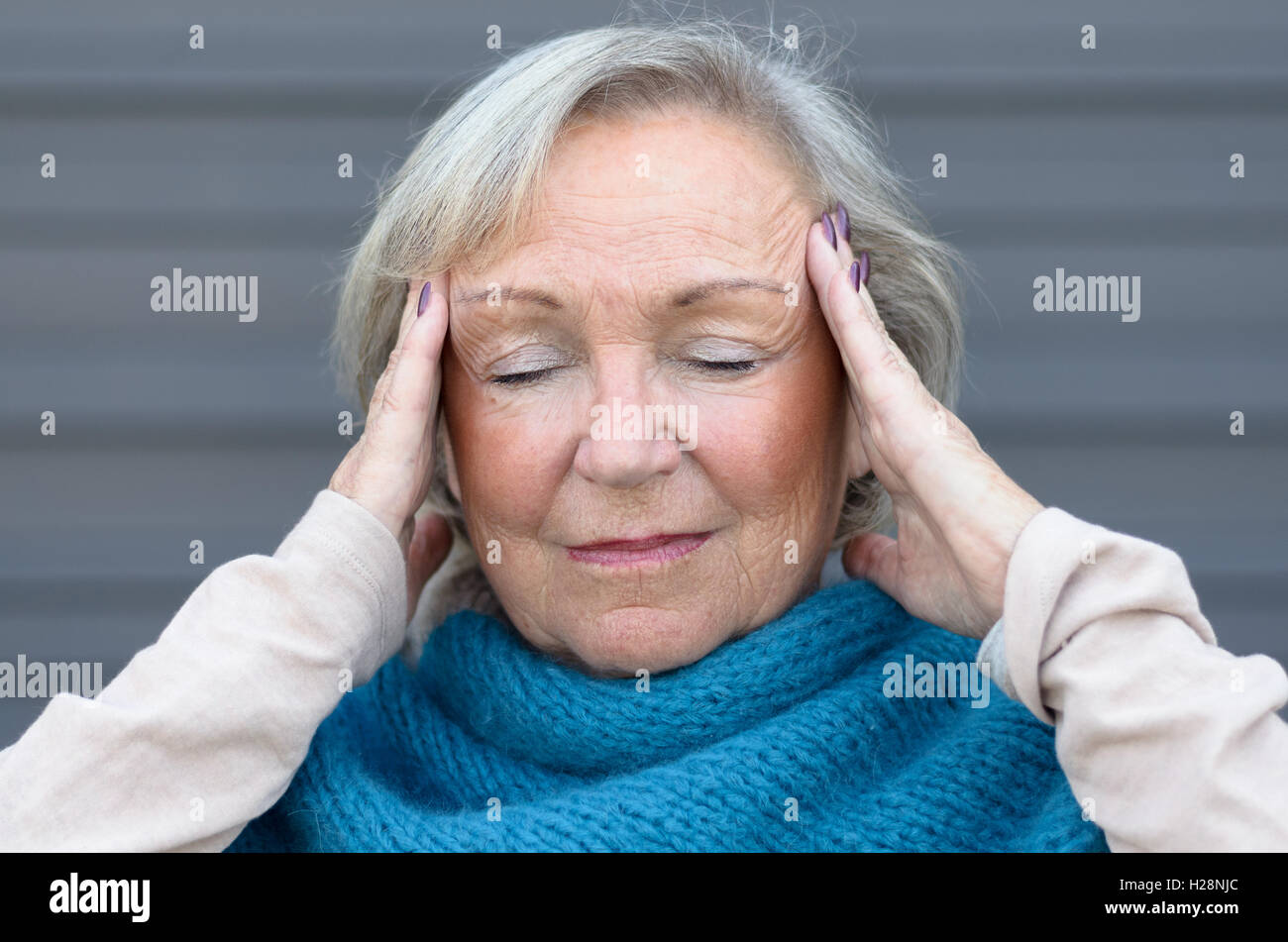 Senior woman holding her hands to her temples with her eyes closed as she takes a quiet moment to de-stress from - Stock Image
