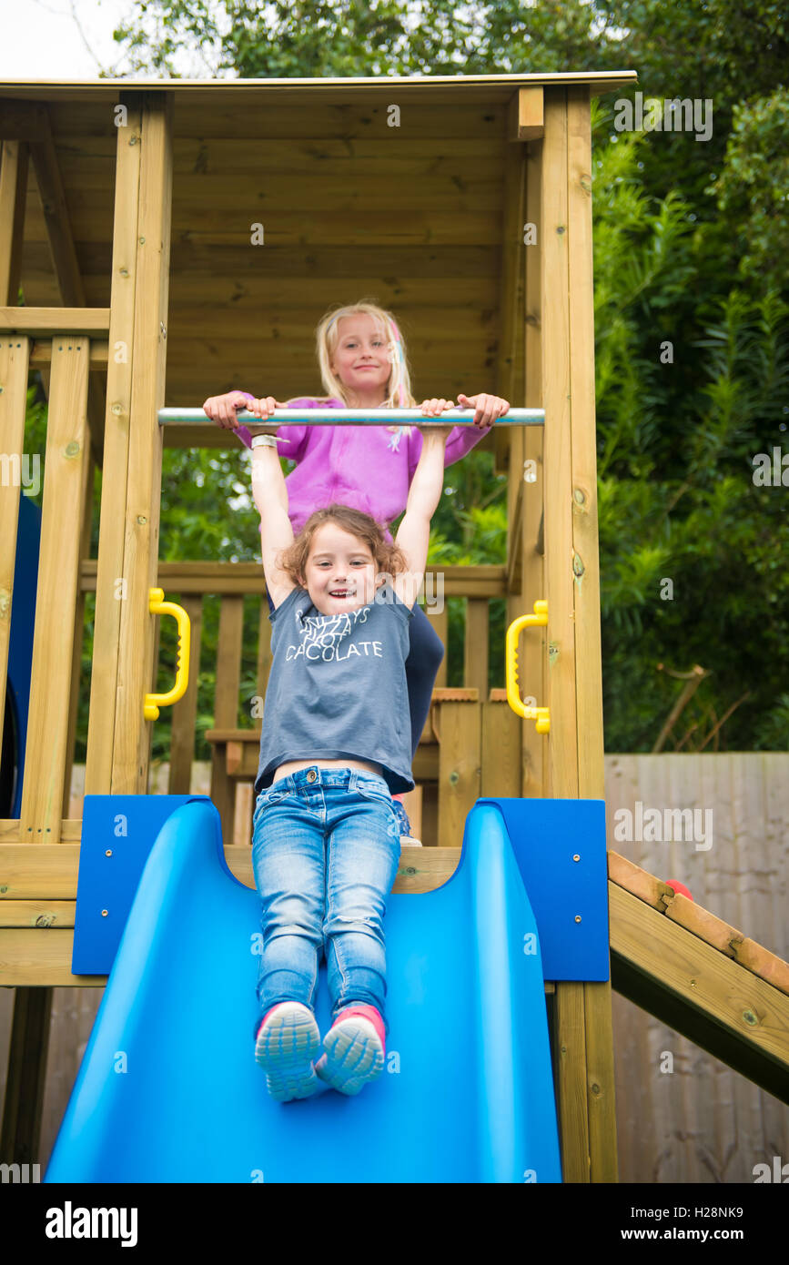 Two young girls on a slide. - Stock Image