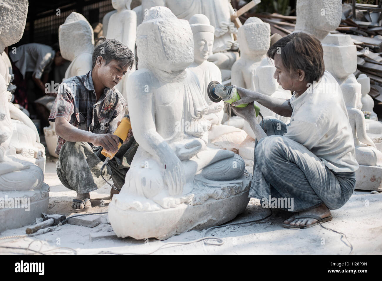 Local men carving a marble Buddha statue using an angle grinder, Amarapura, near Mandalay, Myanmar. - Stock Image