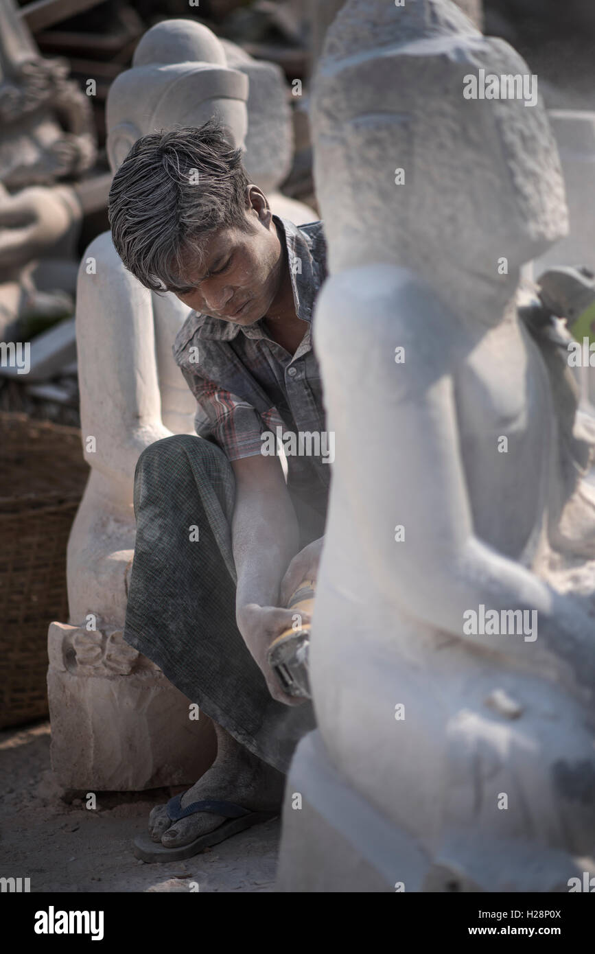 A local man carving a marble Buddha statue using an angle grinder, Amarapura, near Mandalay, Myanmar. - Stock Image