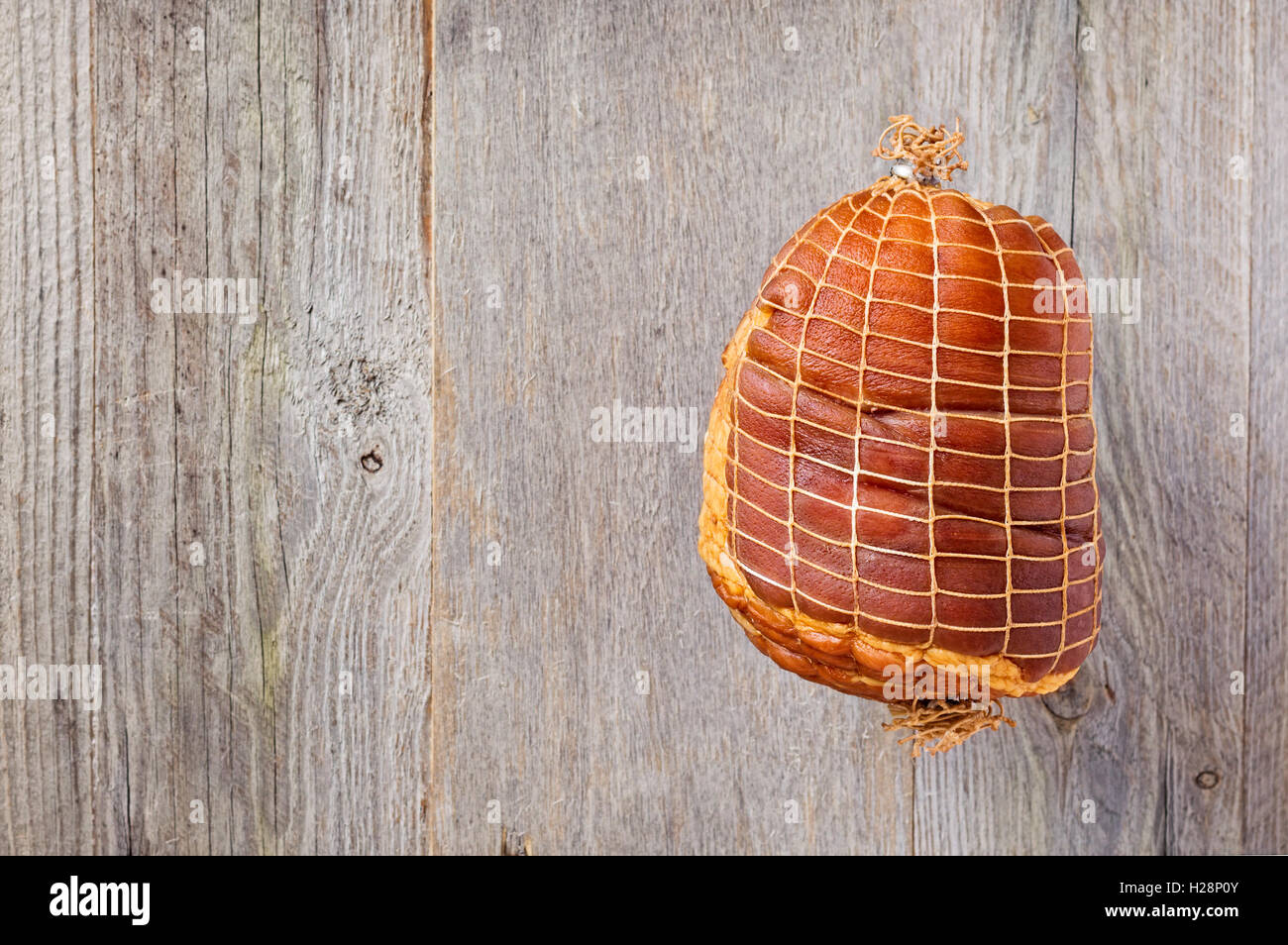 Smoked boneless pork ham hock wrapped in netting on a weathered wood background - Stock Image