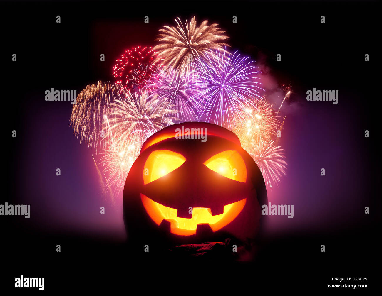 Halloween Fireworks Party. Glowing Jack O' Lantern pumpkin with a fireworks display event. - Stock Image