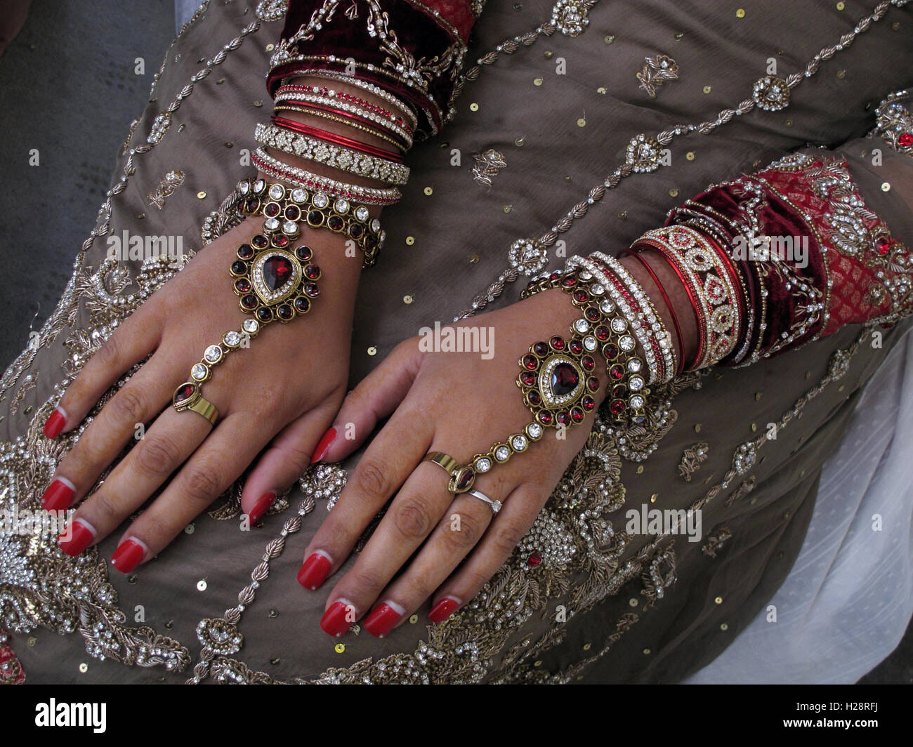 Asian wedding hands and jewelery, henna and gold - Stock Image