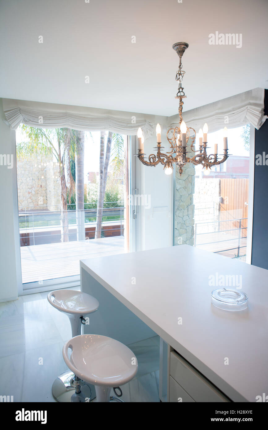 Modern white kitchen table with vintage chandelier Stock ...