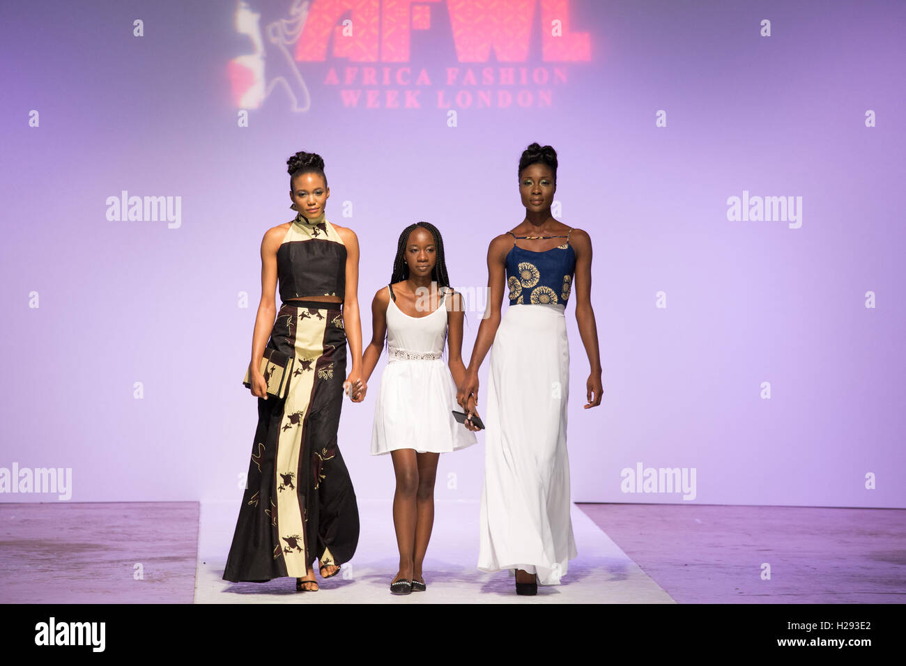 Tiza designer walking down th runway with two models who showcased her collection at the Africa Fashion Week London. - Stock Image
