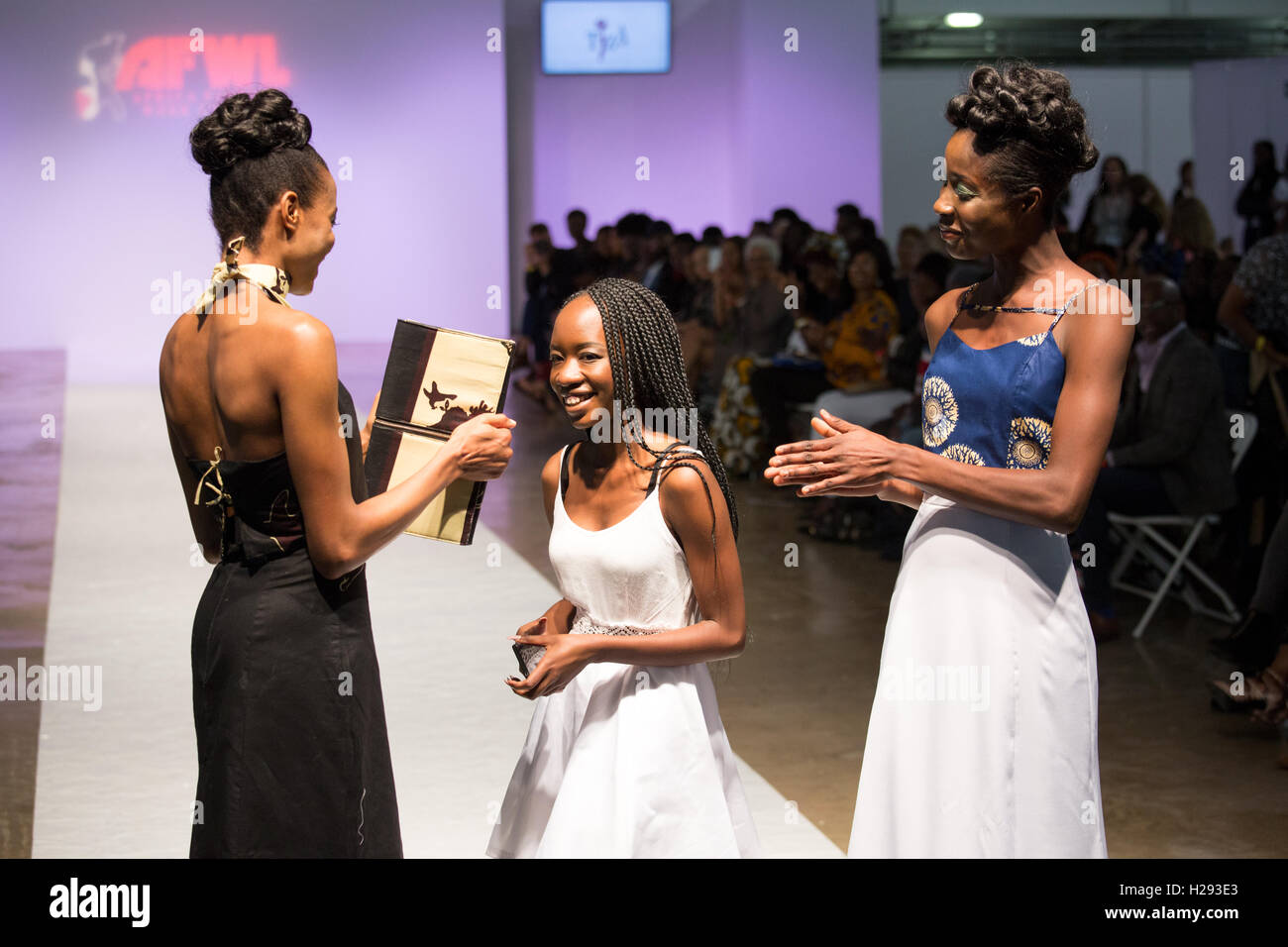 Tiza designer acknowledge applause from public and two models who showcased her collection at the AFWL at the Kensington - Stock Image