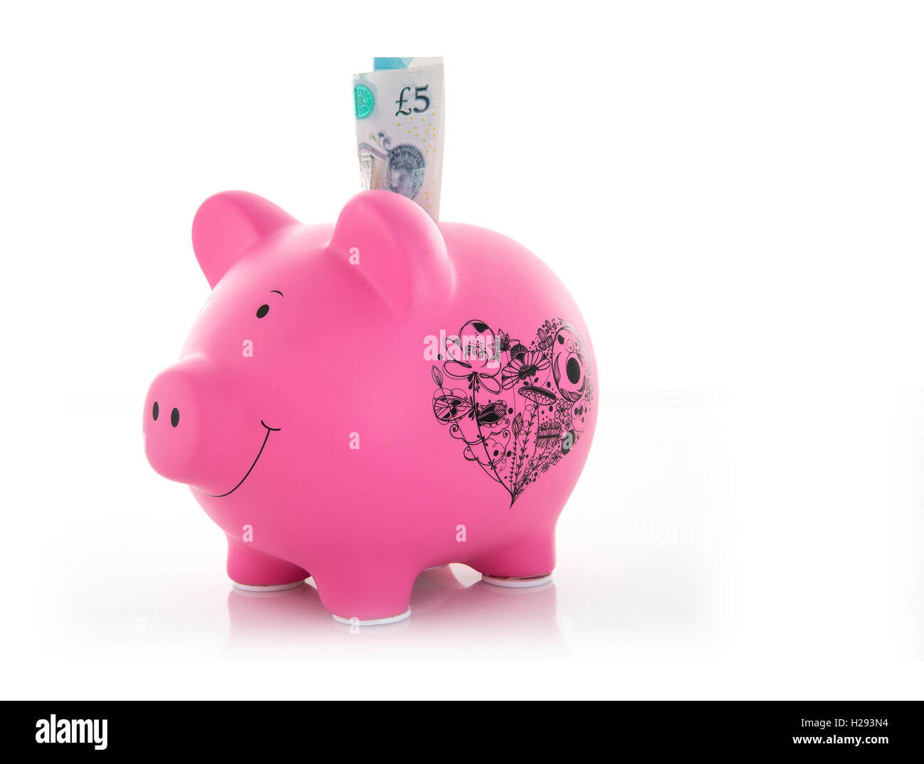 Pink Piggy Bank with new five pound note on a white Background - Stock Image