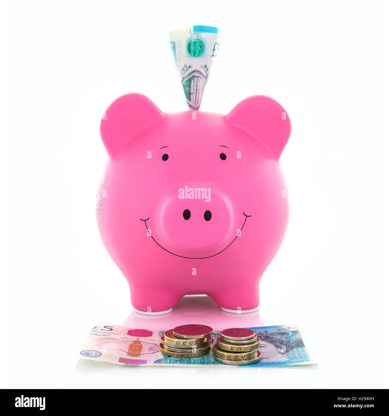 Pink Piggy Bank with new polymer five pound notes on a white Background - Stock Image