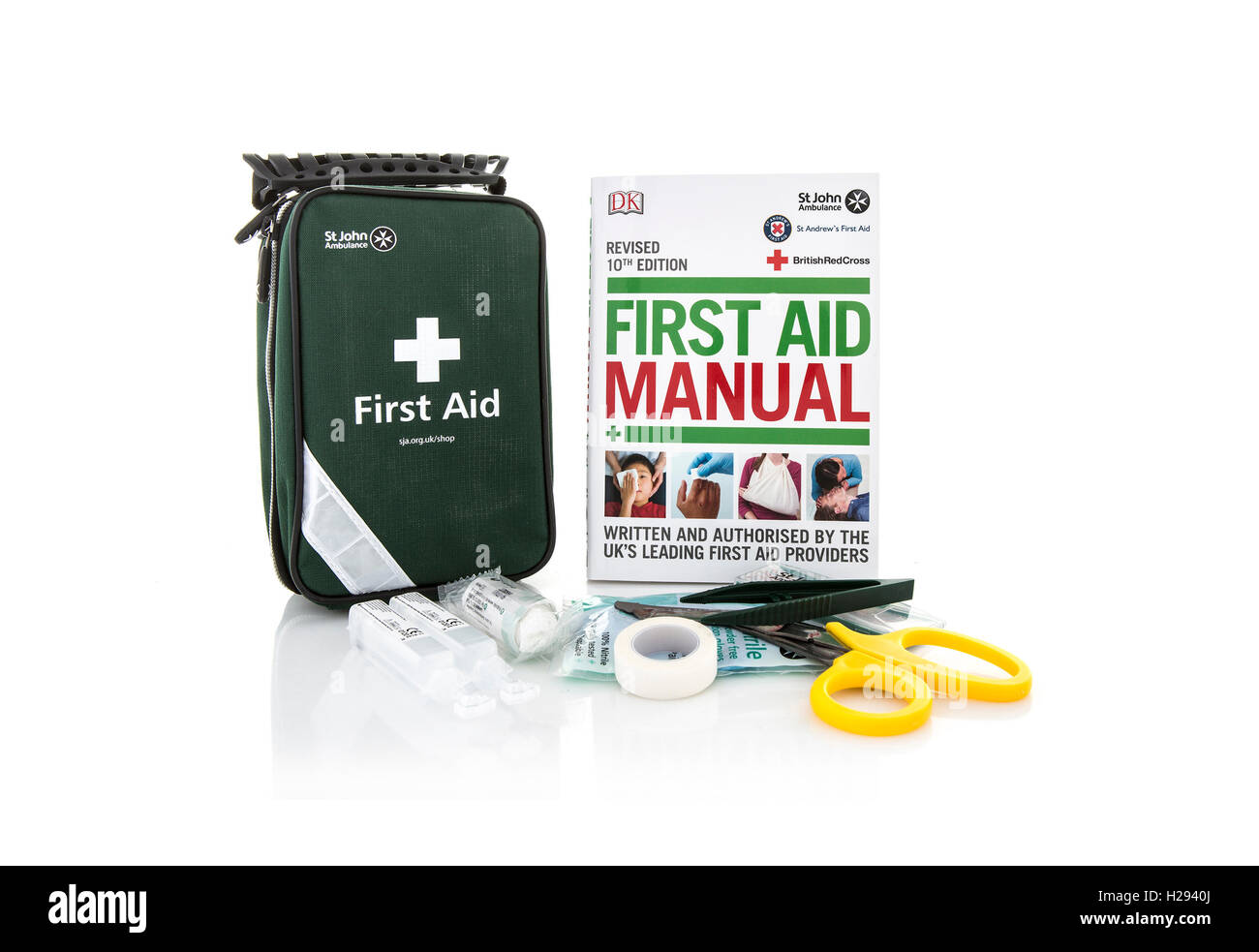 St John Ambulance First Aid Kit and Manual on a white background - Stock Image