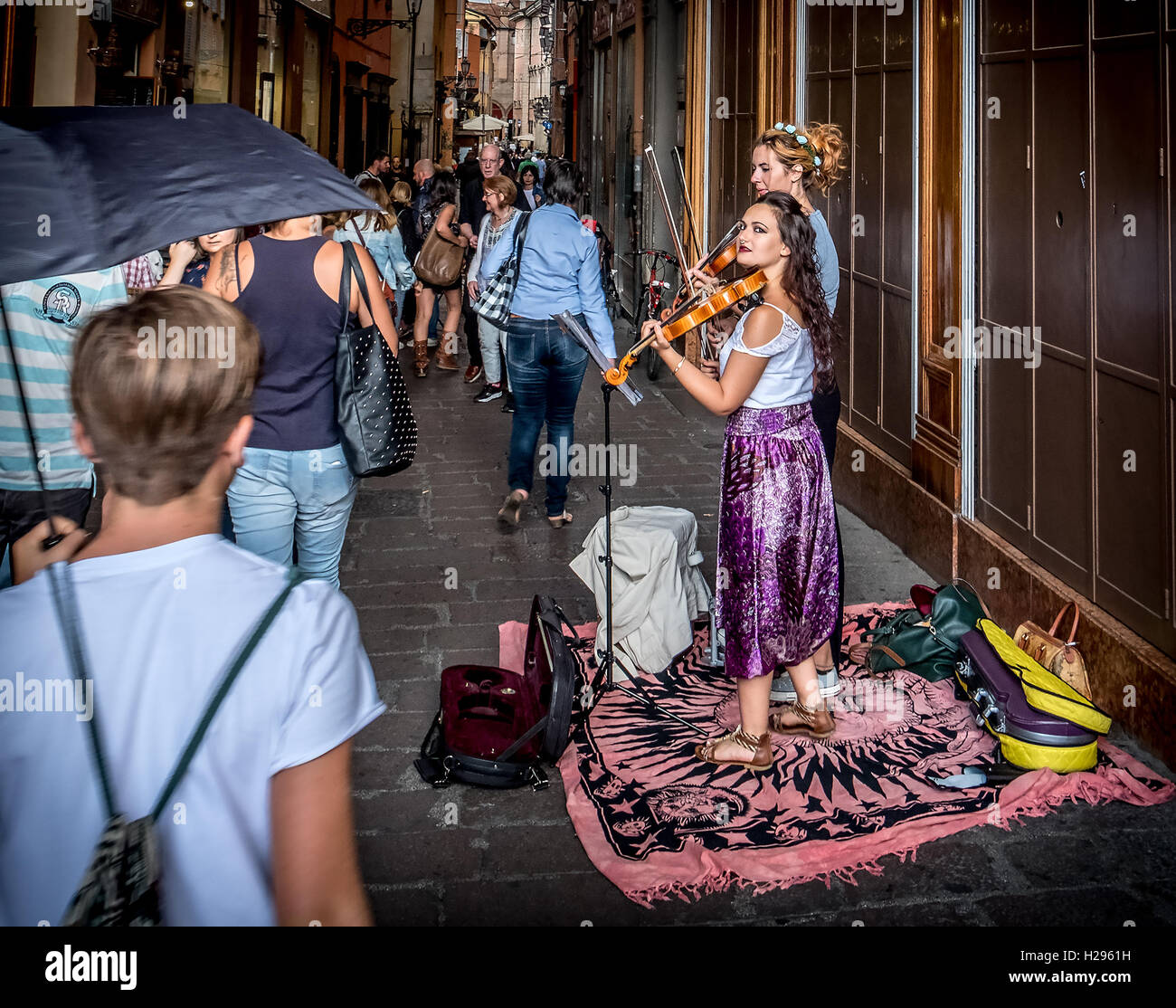 two buskers violinists perform for the passersby in the historic district of Bologna. - Stock Image