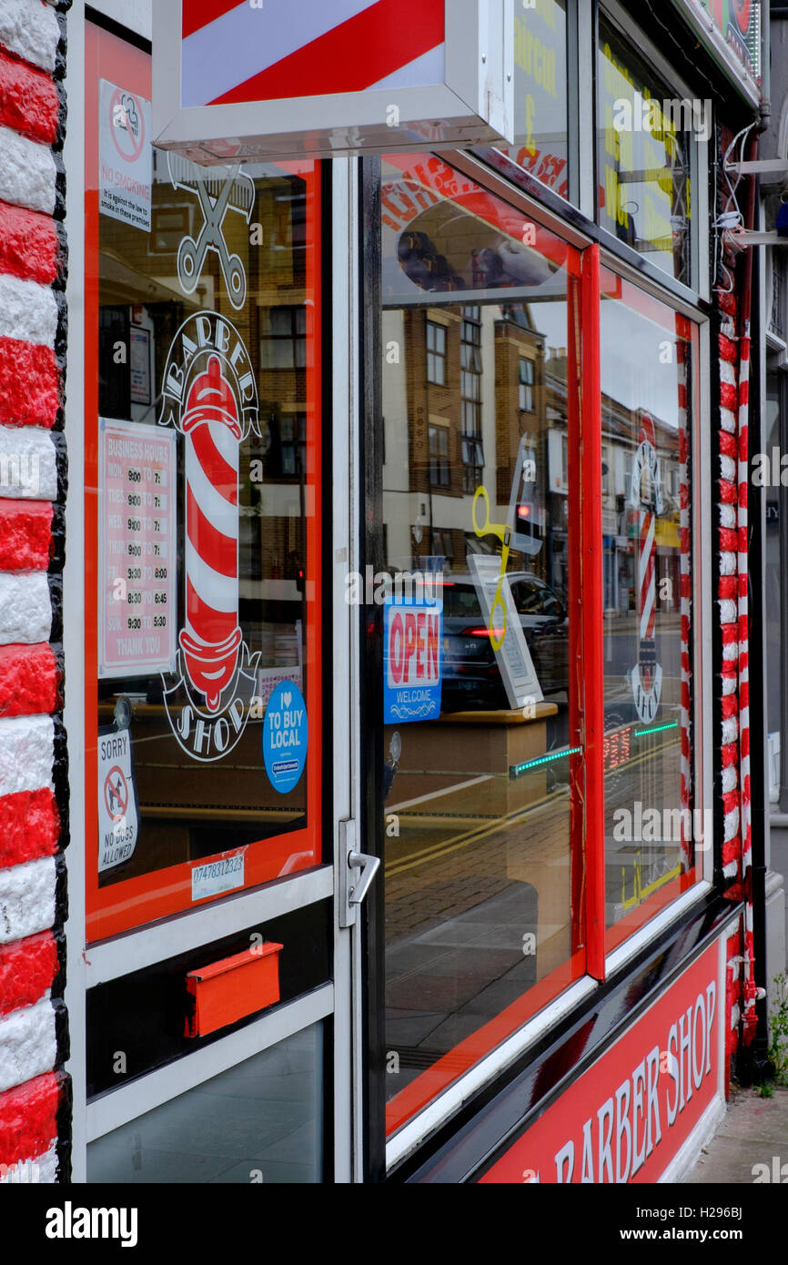 traditional barbers with a red and white striped exterior uk - Stock Image