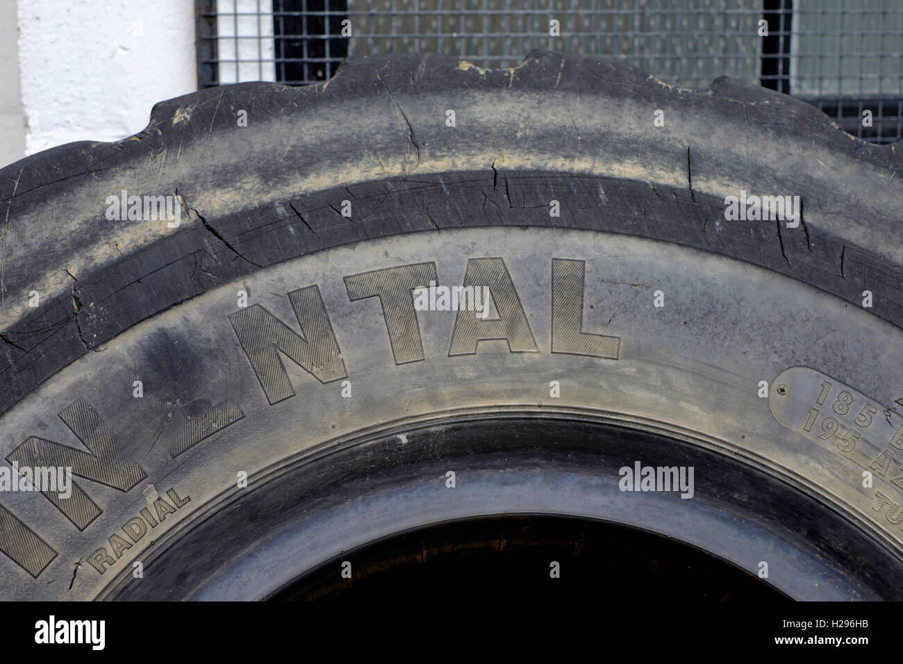 large worn out industrial sized commercial tyres dumped in a yard uk - Stock Image