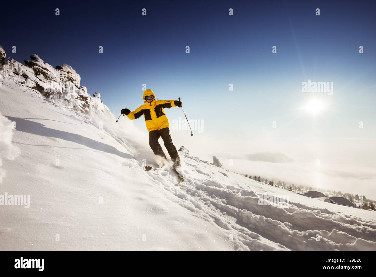 Snowboarder rides on blue sky backdrop in mountains - Stock Image