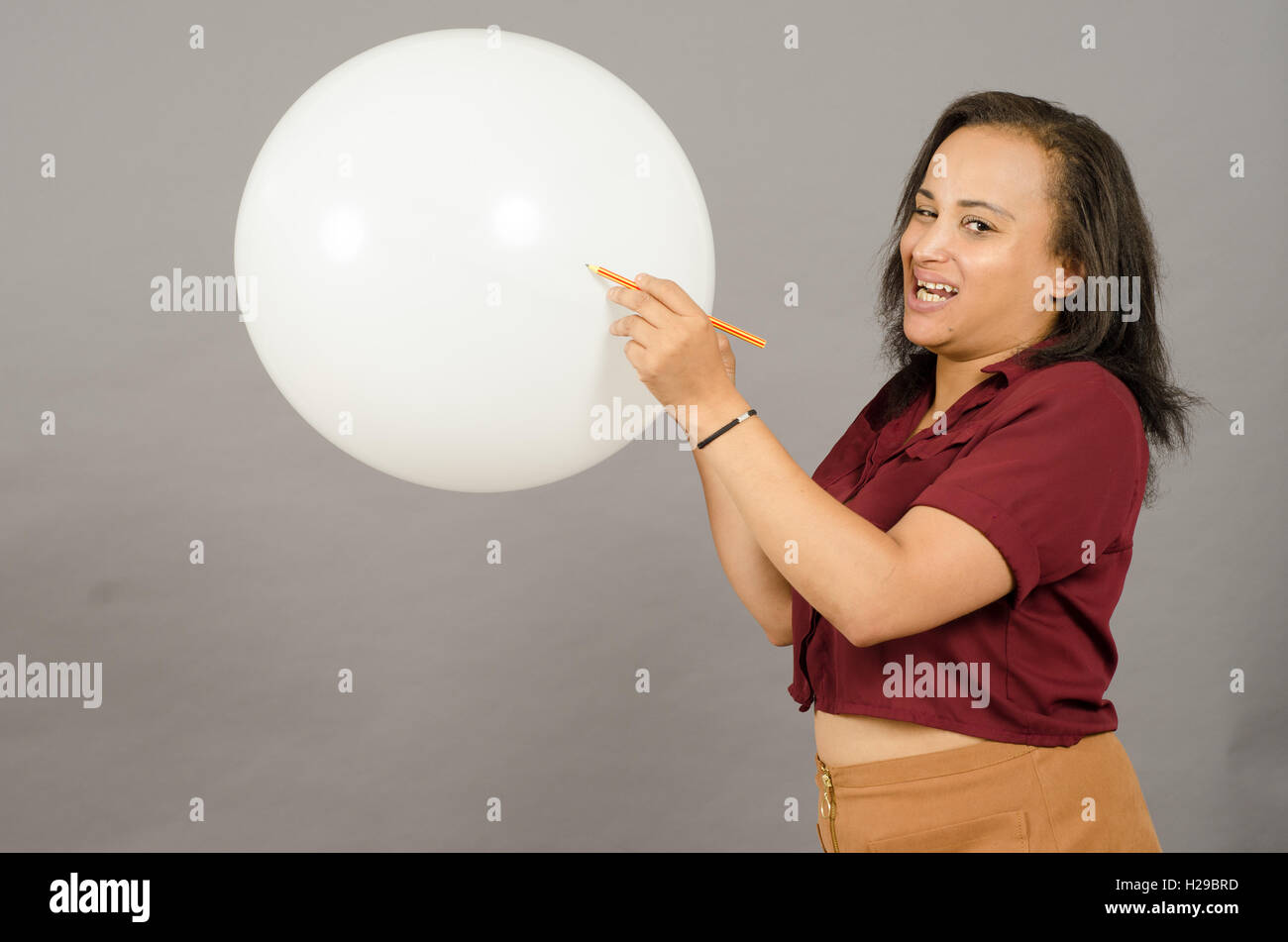 Adult woman bursting a big white balloon with a pencil. - Stock Image